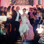A wedding couple on the grand marble staircase surrounded by guests thumbnail