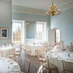 A round table lunch layout in a room with large windows and a golden chandelier thumbnail