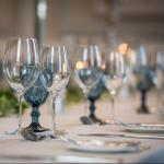 Wine glasses and crockery set on a dinner table with candles  thumbnail